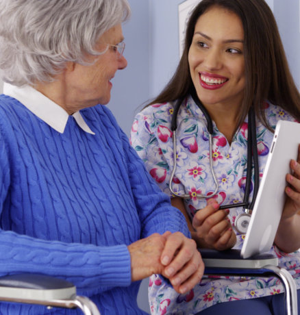 caregiver talking to elderly patient with tablet